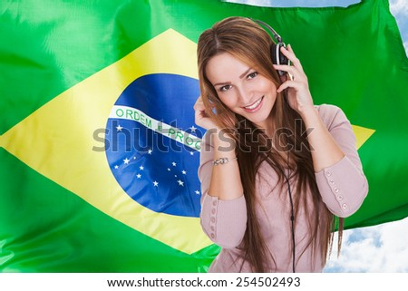 Woman Listening Brazilian Language Learning Audiobook On Headphones In Front Of Brazilian Flag - stock photo