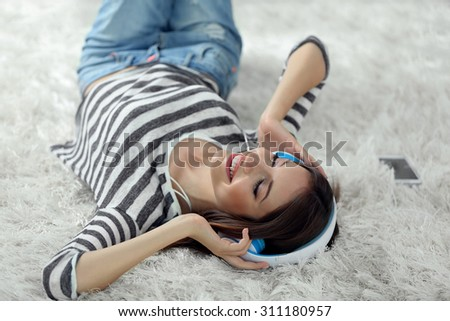 Woman listening music in headphones on carpet in room - stock photo