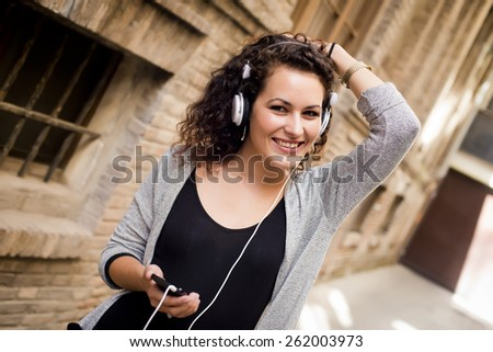 Woman listening music in the street - stock photo