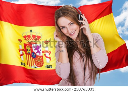 Woman Listening Music On Headphones In Front Of Spanish Flag - stock photo