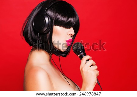 Woman listening to music on headphones enjoying a dance. Closeup portrait of beautiful girl with pink lips - stock photo
