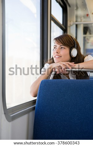 Woman listening to music on train - stock photo