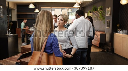 Woman listening with concern to friend in busy cafe - stock photo