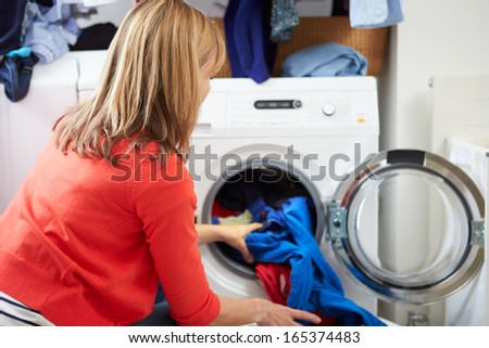 Woman Loading Clothes Into Washing Machine - stock photo