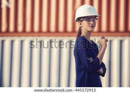 woman logistics engineer is standing in front of containers - stock photo