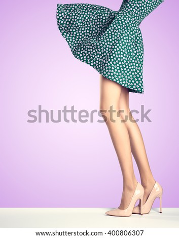 Woman long legs in fashion dress, high heels. Perfect female  sexy legs, stylish blue skirt and summer glamour shoes on purple. Unusual creative elegant walking out outfit, people. Vintage, copy space - stock photo