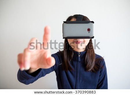 Woman look though vr device and touch on air - stock photo