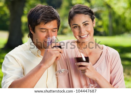 Woman looking ahead and smiling while her friend drinks from a glass of red wine in a park - stock photo