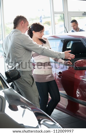 Woman looking at a car interior being pointed by a salesman - stock photo