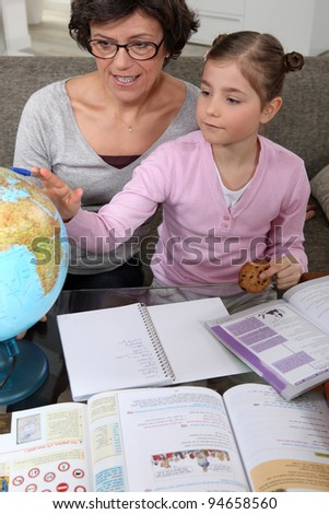Woman looking at a globe with a little girl - stock photo
