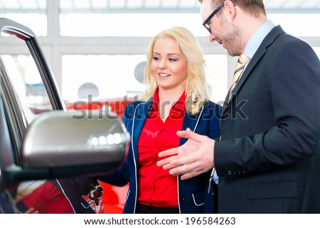 Woman looking at car in auto dealership - stock photo