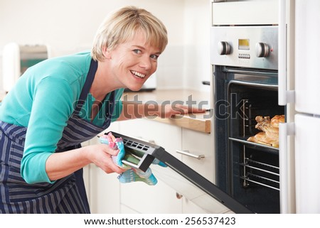 Woman Looking At Chicken Roasting In Oven - stock photo