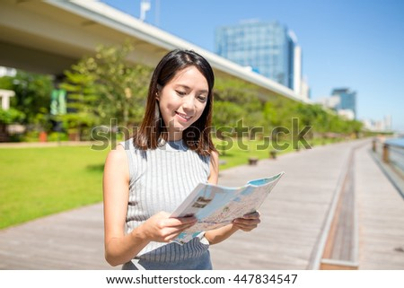 Woman looking at city map - stock photo