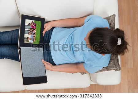 Woman Looking At Family Photo Album While Sitting On Sofa At Home - stock photo
