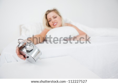 Woman looking at her alarm clock while lying in her bed - stock photo