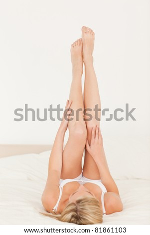 Woman looking at her legs in her bedroom - stock photo