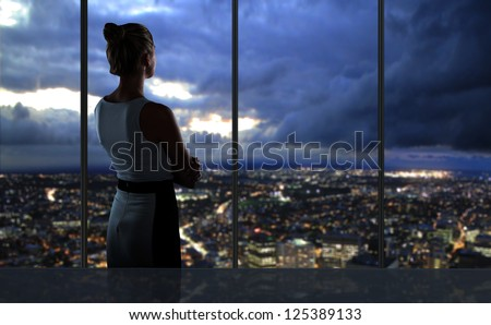 woman looking at night city - stock photo