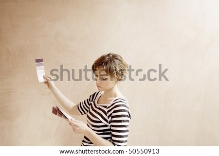 Woman looking at paint colour swatches in unrenovated room - stock photo
