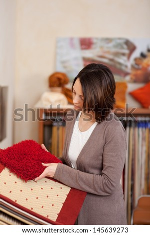 Woman looking at red carpet samples deciding on the color and texture best suited to her new house interior - stock photo