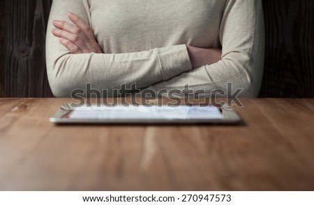 woman looking at  screen digital tablet over wooden table - stock photo