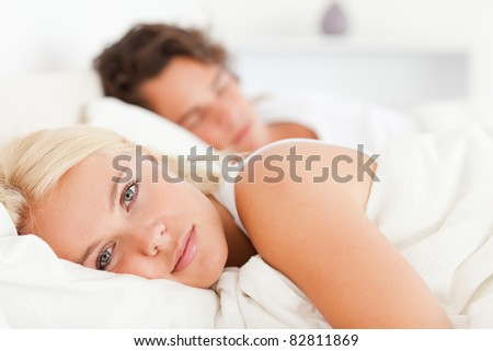 Woman looking at the camera while her fiance is sleeping in their bedroom - stock photo