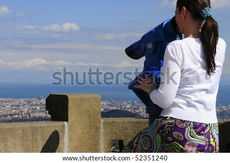 Woman looking at the city of Barcelona from Tibidabo, using a coin operated pair of binoculars. - stock photo