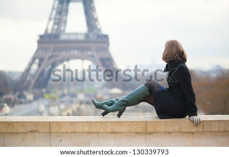 Woman looking at the Eiffel tower - stock photo
