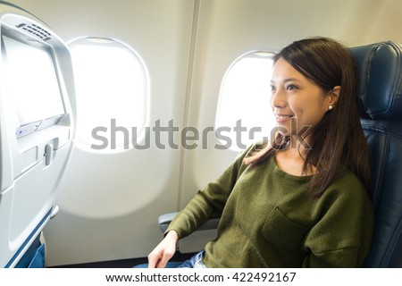 Woman looking at the window of the airplane - stock photo