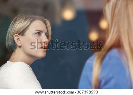 Woman looking concerned while listening carefully to her friend - stock photo