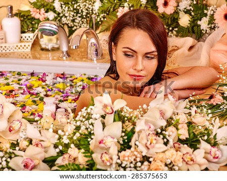 Woman looking down relaxing at water flower spa. - stock photo