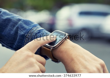 Woman looking for her car with smart-watch in parking car - stock photo