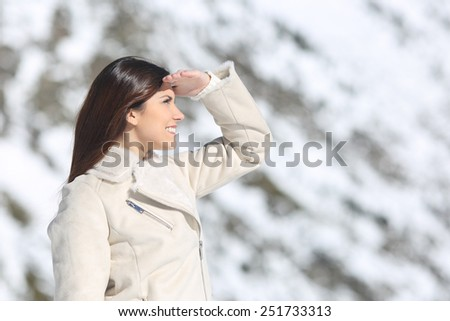 Woman looking forward with the hand on forehead in winter holidays with a snowy mountain in the background - stock photo