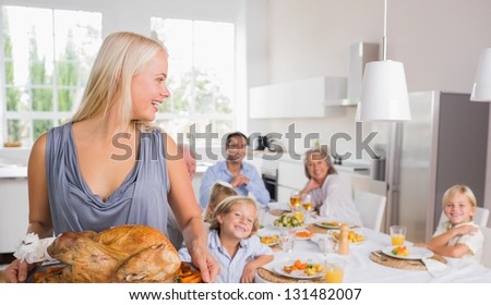 Woman looking her family and holding a turkey - stock photo
