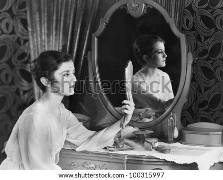 Woman looking in mirror - stock photo