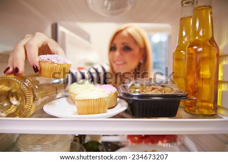 Woman Looking Inside Fridge Full Of Unhealthy Food - stock photo