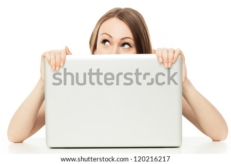 Woman looking out from behind a laptop - stock photo