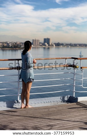 Woman looking out into bay from public walkway. 