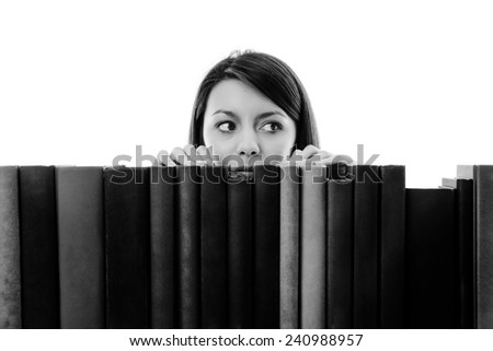 woman looking over books on a bookshelf - stock photo
