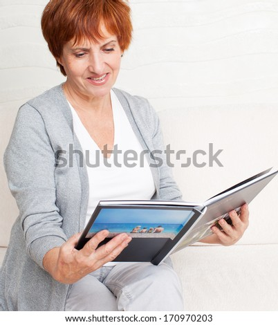 Woman looking photo book. Mature woman looking photography album - stock photo