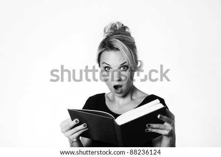 woman looking surprised what she just read in a book - stock photo
