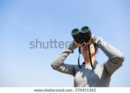 Woman looking though binoculars - stock photo