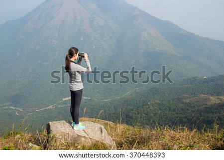 Woman looking though binoculars at mountain - stock photo