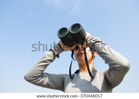Woman looking though telescope - stock photo