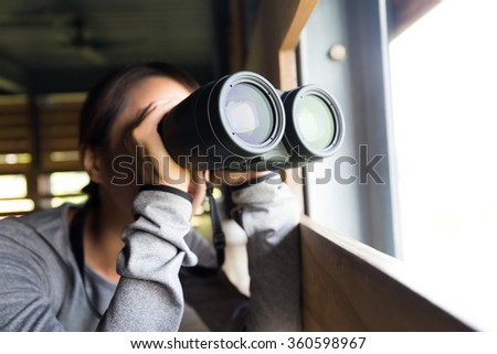 Woman looking though the binoculars at wooden house - stock photo