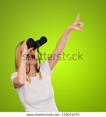 Woman Looking Through Binoculars against a green background - stock photo