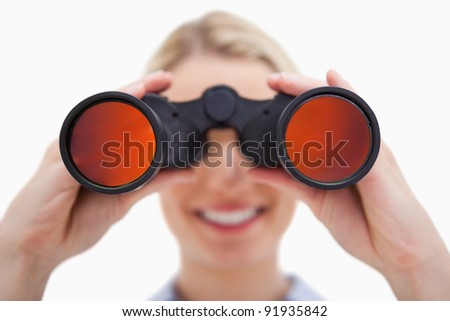 Woman looking through binoculars against a white background - stock photo