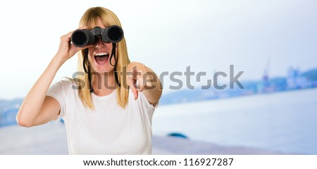 woman looking through binoculars and pointing, outdoor - stock photo