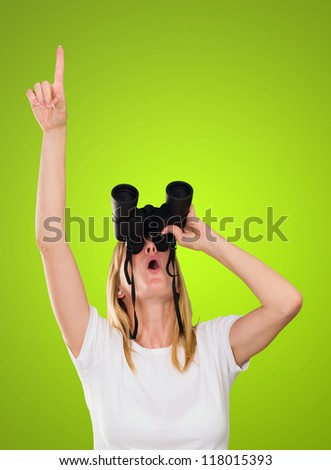 woman looking through binoculars and pointing up against a green background - stock photo