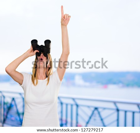 woman looking through binoculars and pointing up, outdoor - stock photo