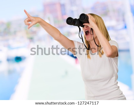 Woman Looking Through Binoculars at a port - stock photo